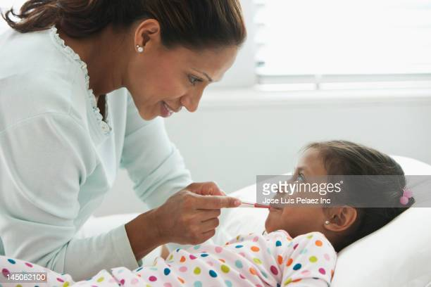 Hispanic mother taking daughter's temperature