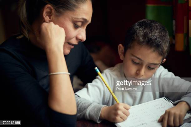 hispanic mother watching son practicing writing alphabet - homeschool ストックフォトと画像