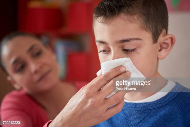 hispanic mother wiping nose of son with tissue - rubbing stock photos and pictures