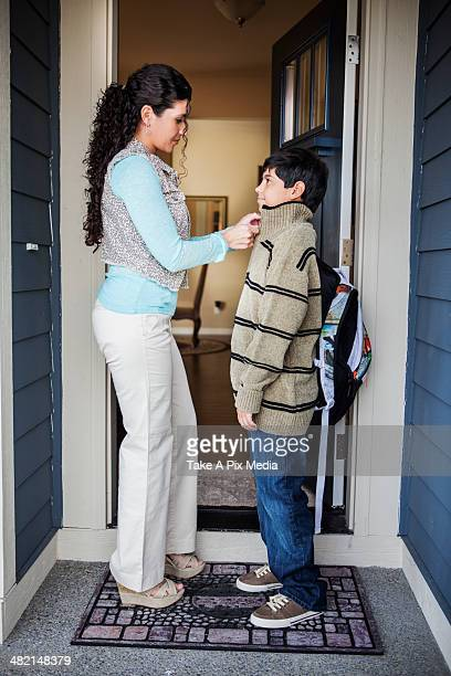 Hispanic mother zipping son's jacket at door