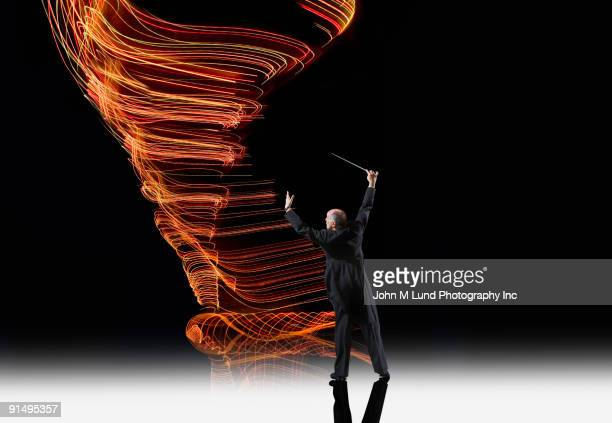 Hispanic musical conductor in front of light trails