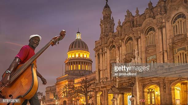 Hispanic musician carrying upright bass in city, Havana, Cuba