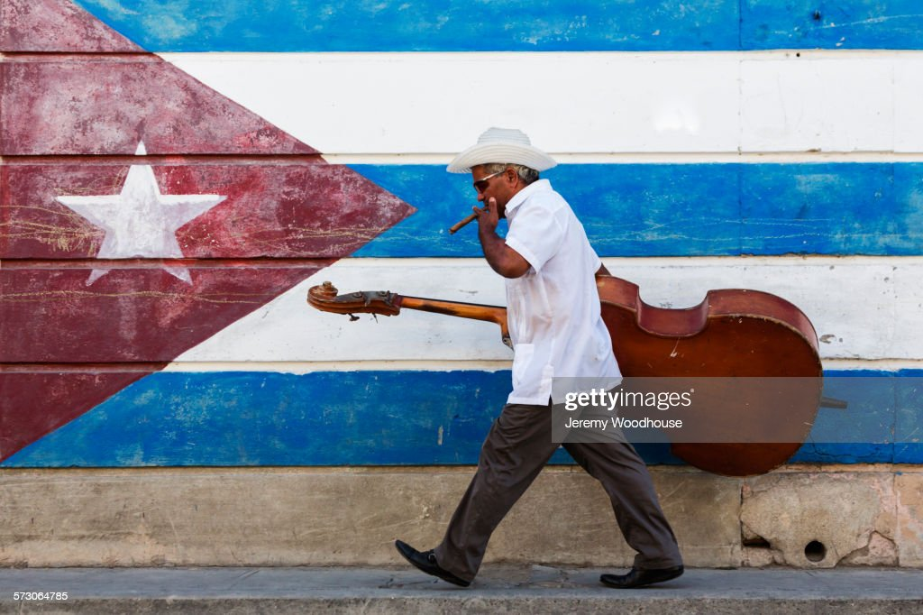 Hispanic musician carrying upright bass in front of Cuban flag mural : ストックフォト