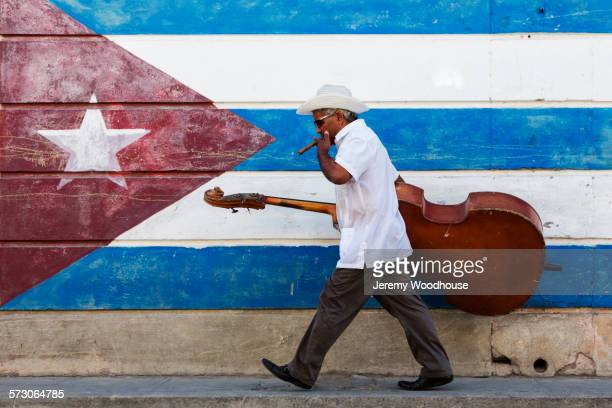 hispanic musician carrying upright bass in front of cuban flag mural - cuba foto e immagini stock