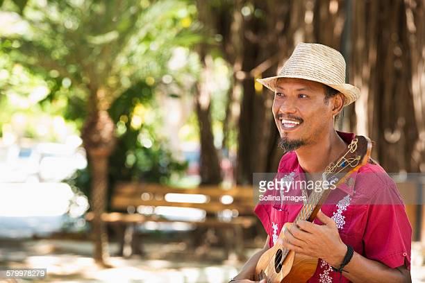 hispanic musician playing ukulele in park - ukulele stock pictures, royalty-free photos & images