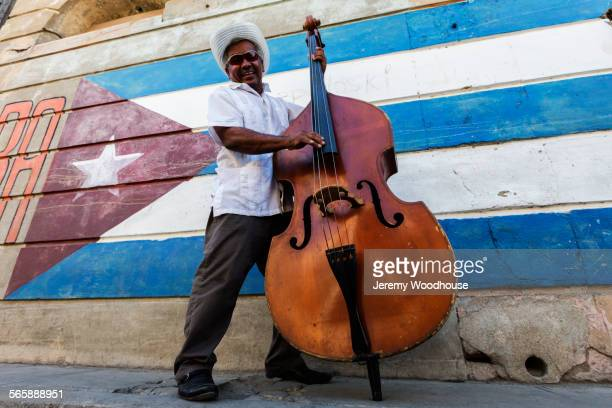 hispanic musician playing upright bass near cuban flag, santiago de cuba, santiago, cuba - cuba foto e immagini stock