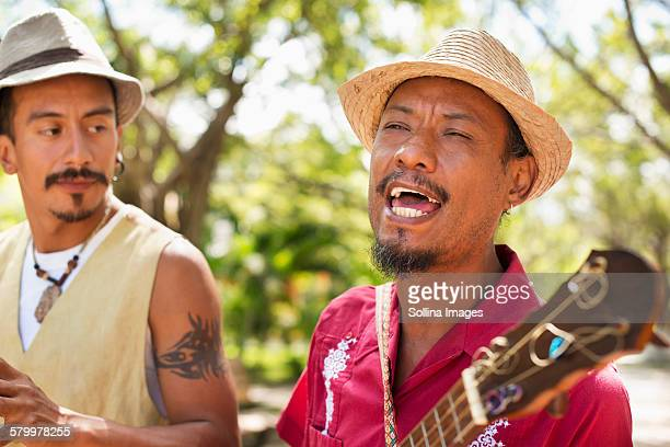 hispanic musicians performing in park - street artist stock photos and pictures
