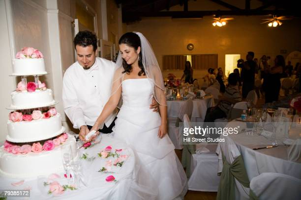Hispanic newlyweds cutting wedding cake