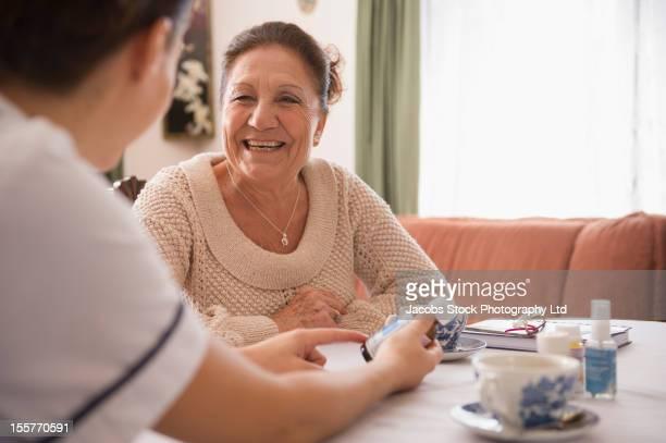 Hispanic nurse explaining medication senior woman