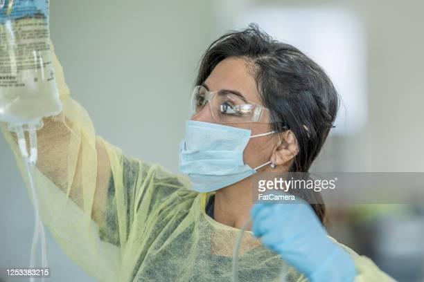hispanic nurse hanging an iv bag - iv drip stock pictures, royalty-free photos & images