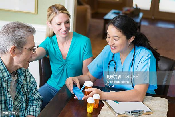 Hispanic nurse visits with senior patient in his home