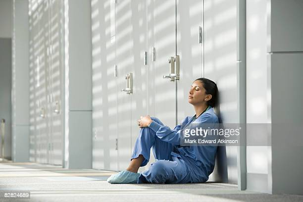 Hispanic nurse with eyes closed sitting on floor