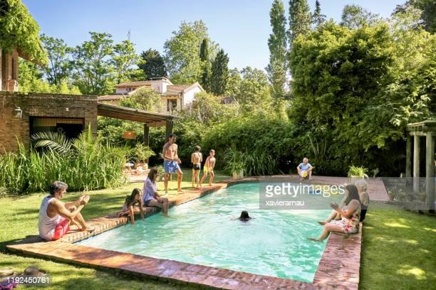 parents et enfants hispaniques ayant l'amusement à la piscine de famille - piscine photos et images de collection