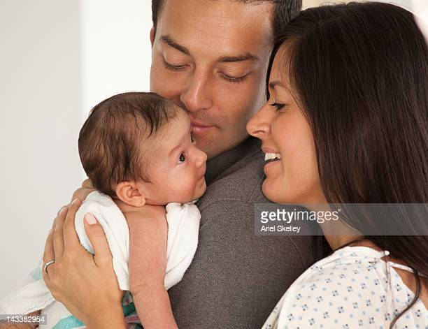 Hispanic parents looking at newborn baby