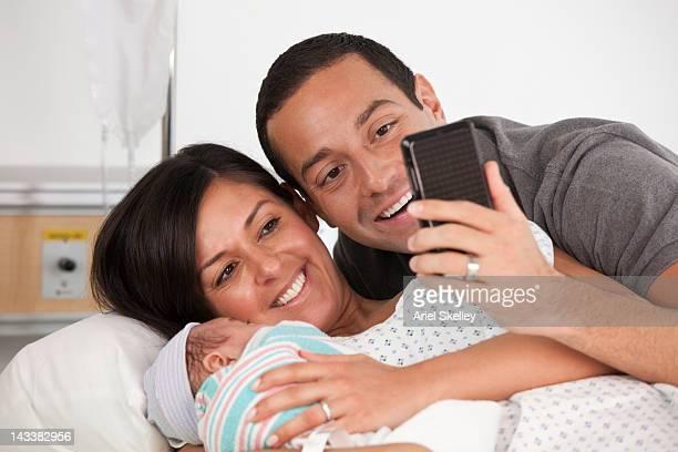 Hispanic parents taking photograph of newborn baby