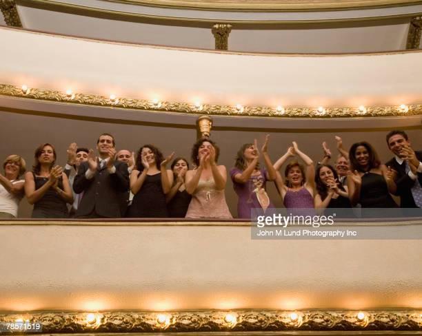 Hispanic people applauding in balcony