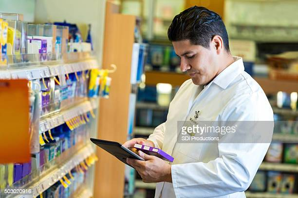 Hispanic pharmacist checking inventory with digital tablet