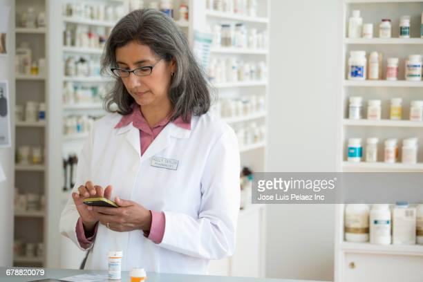 Hispanic pharmacist texting on cell phone in pharmacy