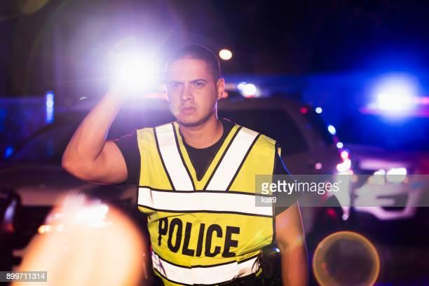 Hispanic police officer at night, flashing lights