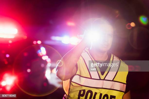 hispanic police officer at night, flashing lights - police lights stock pictures, royalty-free photos & images