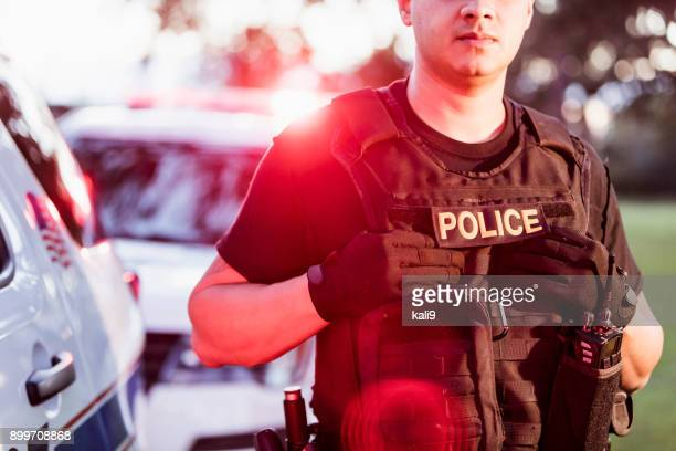 hispanic police officer wearing bulletproof vest - police force stock pictures, royalty-free photos & images