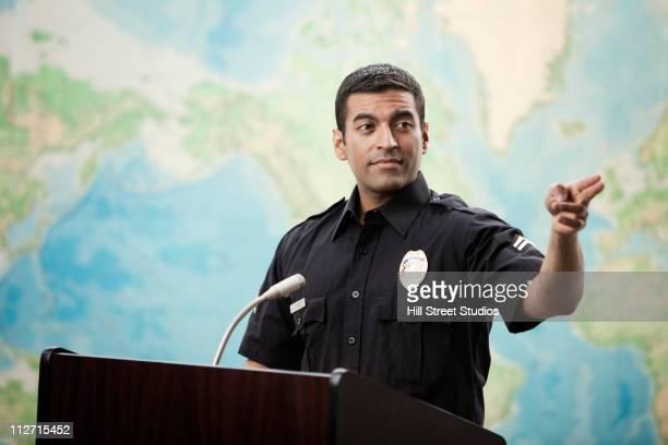 Hispanic policeman parado en podium