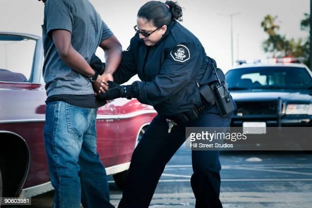 Hispanic policewoman handcuffing man