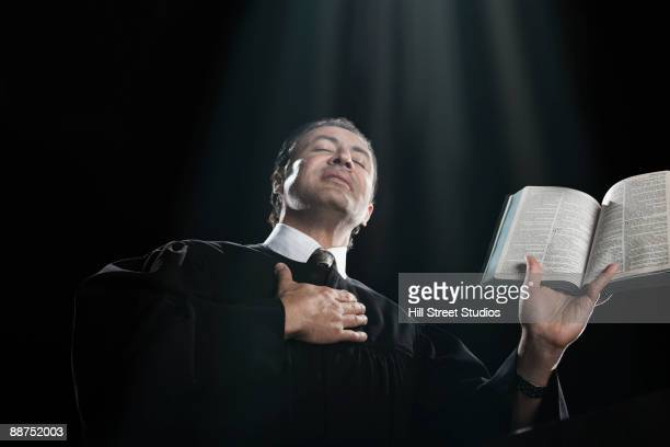 Hispanic priest holding bible with eyes closed