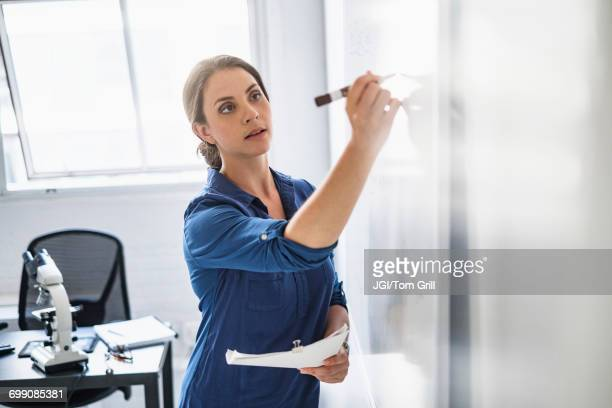 hispanic professor writing on whiteboard - cancer illness stock photos and pictures