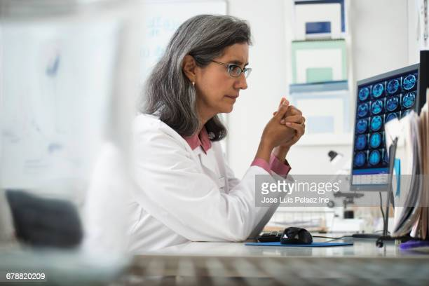 hispanic radiologist using computer at desk - radiologist stock pictures, royalty-free photos & images
