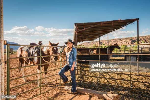 Hispanic rancher smiling near horses