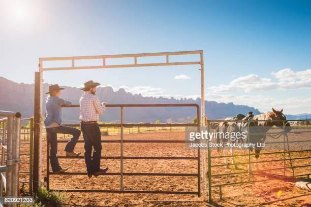 hispanic ranchers standing on gate - 家畜柵 ストックフォトと画像