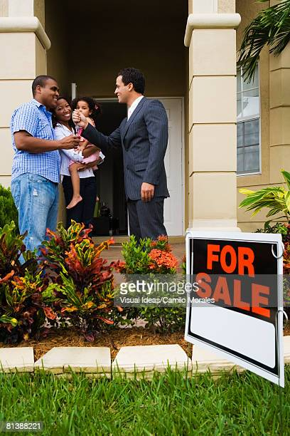 Hispanic real estate agent giving house keys to African family