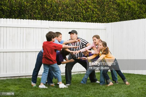 Hispanic referee between groups of boys and girls