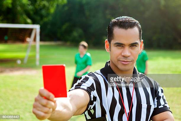 hispanic referee holds a red penalty card during soccer game - carton rouge photos et images de collection