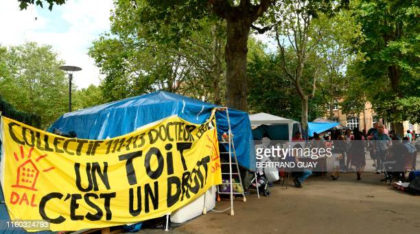 Hispanic refugees stand next to a banner reading A house is a right on the forecourt of the town hall of SaintOuen near Paris on August 8 2019 Around...