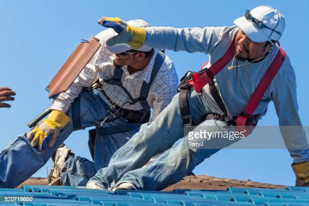 Hispanic Roofer Tossing Old Piece of Tile to Another During a Reroof