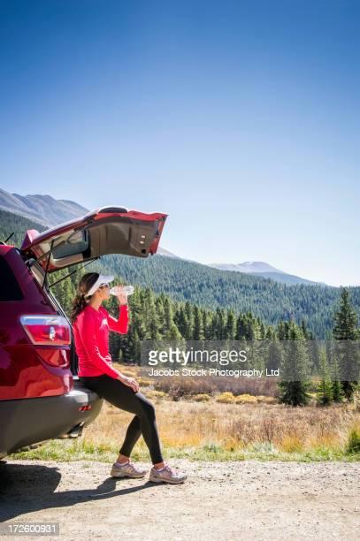 Hispanic runner by car in rural landscape