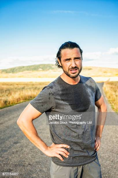 hispanic runner resting in road - sweat stock pictures, royalty-free photos & images