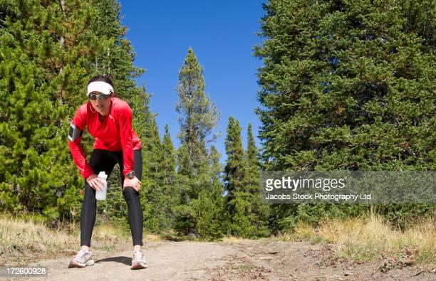 Hispanic runner resting in rural landscape