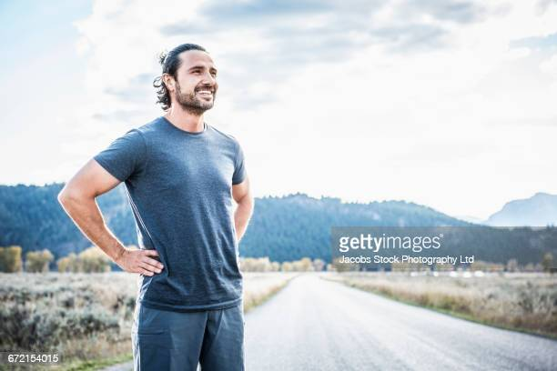 hispanic runner resting near mountain - three quarter length stock pictures, royalty-free photos & images