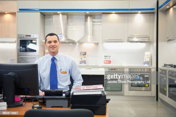 Hispanic salesman smiling in kitchen appliances store
