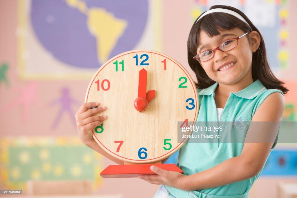 Hispanic school girl holding clock : Stock Photo