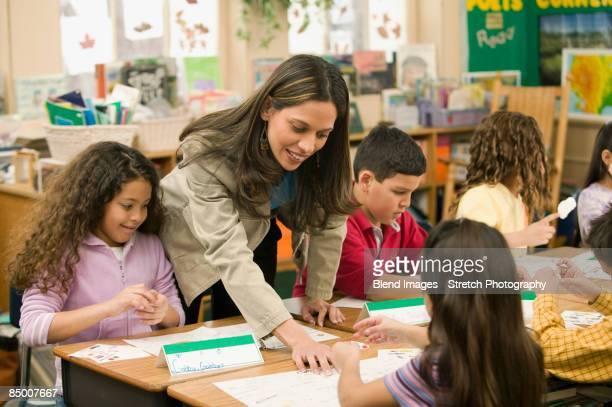 hispanic school teacher helping students - criança de escola fundamental - fotografias e filmes do acervo