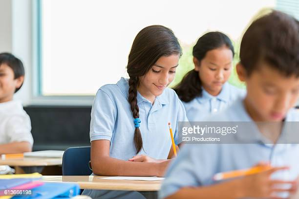 Hispanic schoolgirl concentrates while working on class assignment
