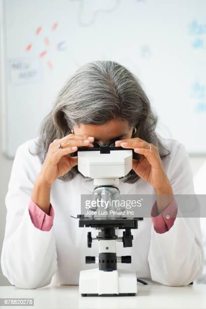 Hispanic scientist using microscope