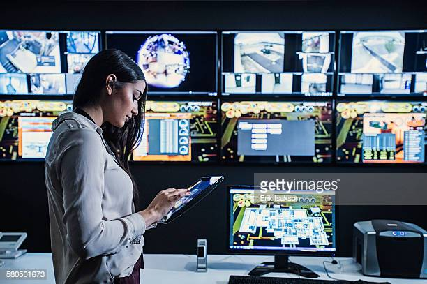 Hispanic security guard using digital tablet in control room