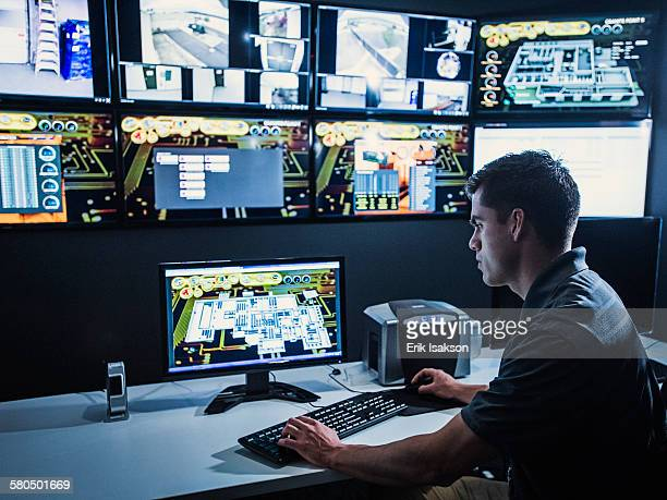 Hispanic security guard watching monitors in control room