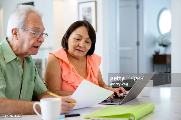 hispanic senior couple using laptop to organize financial planning - document stock pictures, royalty-free photos & images