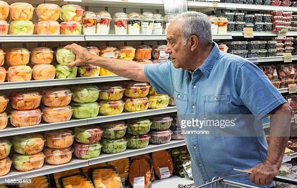 Hispanic senior man buying fruit